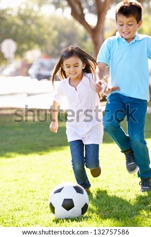 Two Children Playing Soccer Together - stock photo