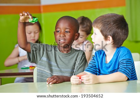 Two children playing together at a table with dough in kindergarten - stock photo