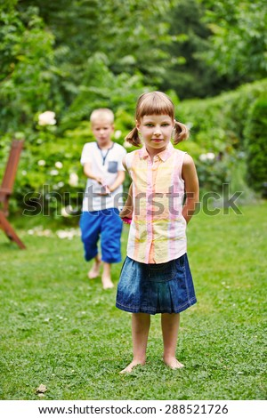 Two children playing together in a garden and pulling a string
