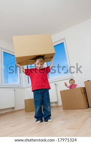 Two children playing with cardboard moving boxes in a room of a new home.