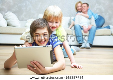 Two children playing with laptop on floor.  Parents sitting on sofa. Selective focus to children. - stock photo