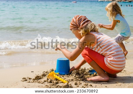 two children playing with sand in the beach - stock photo