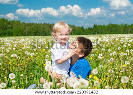 two children plays on a green meadow - stock photo