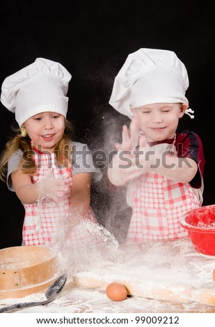 Two children plays with the flour on dark background - stock photo