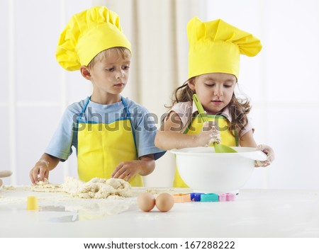 Two children preparing dough in preschool activity - stock photo