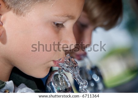 Two children quench their thirst during recess at school - stock photo