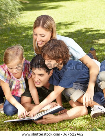 Two children reading book with family in a green garden - stock photo