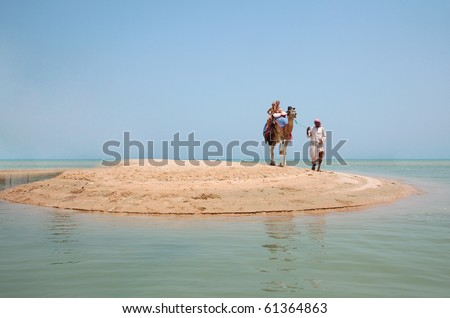 Two children ride a camel on the beach - stock photo