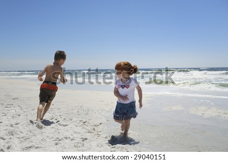 Two children running around with joy on their faces at a beach.