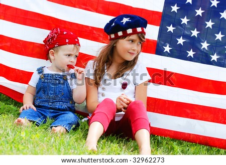 Two children sitting next to an american flag eating suckers - stock photo