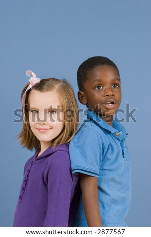 Two children smiling and standing back to back - an African American boy and a Caucasian girl.