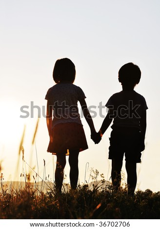 Two children, sunset, romantic scene - stock photo