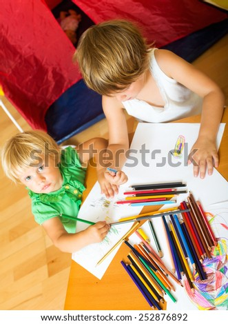 Two children together with pencils in home interior