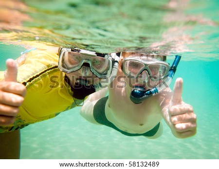 Two children under water in masks - stock photo