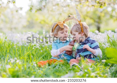 Two children wearing Easter bunny ears at spring green grass and blooming apple garden, eating chocolate bunny and having fun outdoors. On warm sunny day - stock photo