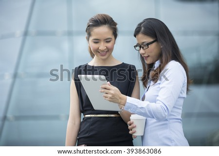 Two Chinese business women with digital tablet in a modern urban setting. - stock photo