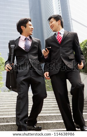 Two Chinese Businessmen Having Discussion Walking Down Steps Outside Office - stock photo