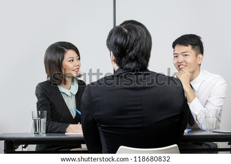 Two Chinese colleagues from hr department interview a male applicant. - stock photo