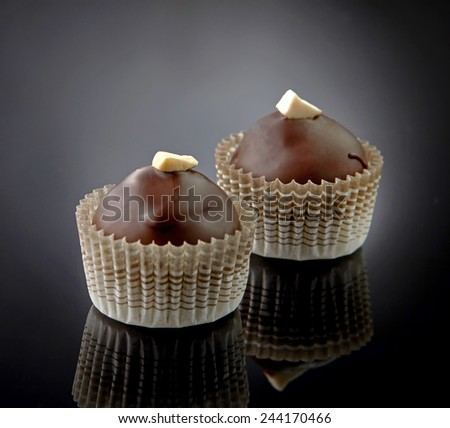 two chocolate candies on black background - stock photo