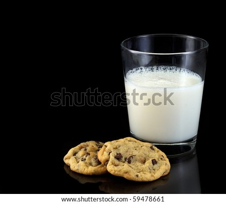 Two chocolate chip cookies and a glass of cold milk on black with copy space - stock photo