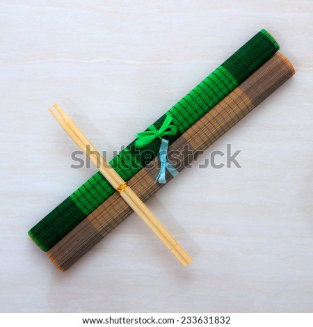 Two chopsticks on two bamboo mats - stock photo