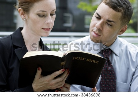 Two Christian coworkers sitting outside reading from the Holy Bible perhaps on their lunch break. - stock photo