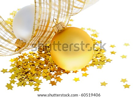 Two christmas balls on heap of confetti stars with yellow ribbon - stock photo
