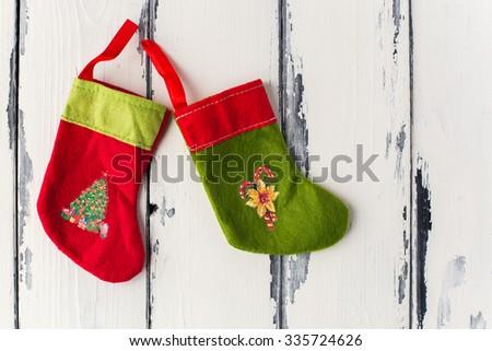 two Christmas Stockings on white vintage wooden background - stock photo