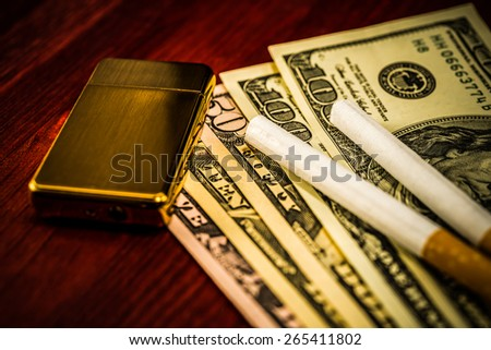 Two cigarettes and golden lighter are on the dollars. Focus on the golden lighter, image vignetting