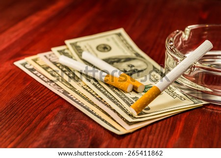 Two cigarettes are on the dollars and other cigarette on the glass ashtray