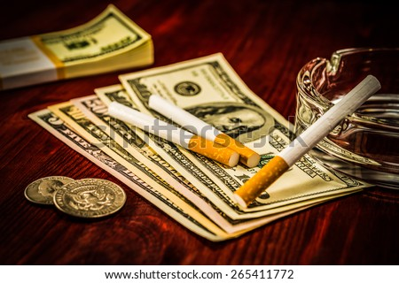Two cigarettes are on the dollars, lies next to a pack of bills and other cigarette on the glass ashtray. Focus on the cigarettes, image vignetting