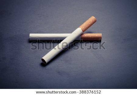 Two cigarettes on a black slate cutting board. Toned. - stock photo