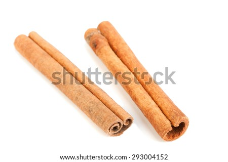 two cinnamon sticks on a white background