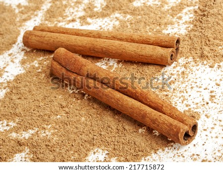 Two cinnamon sticks with its dust around it over a white background - stock photo