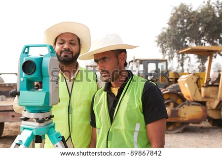 two civil engineers doing land survey at a construction site with construction machinery in the background - stock photo