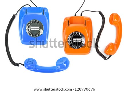 two classic dial phones on white background, minimal natual shadow among objects - stock photo