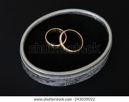Two classic wedding gold rings in a silver gift box on a black background. - stock photo