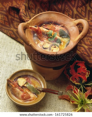Two clay bowls with orange broth and multi colored vegetables. - stock photo