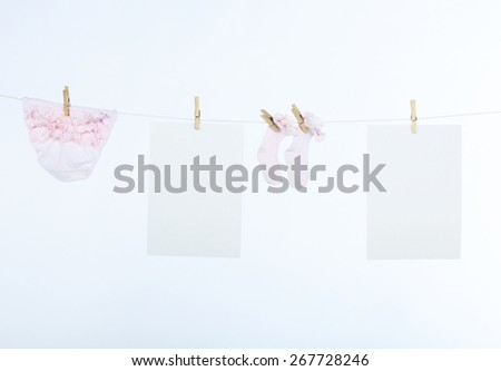 Two clean sheet of paper and baby?s clothes hanging