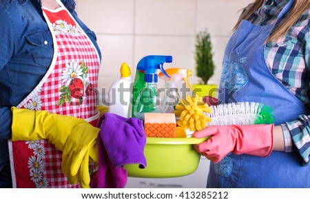 Two cleaning women holding basin full of cleaning supplies in the kitchen. House keeping and teamwork concept - stock photo