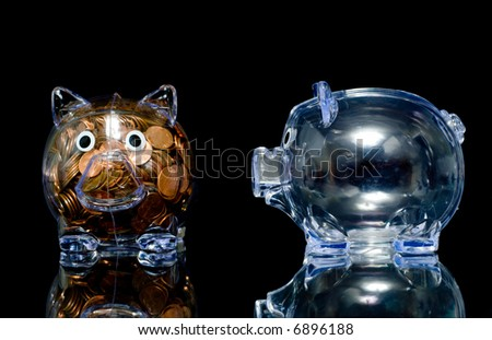 Two clear acryllic piggy banks one stuffed full of american pennies the other empty,.  one pig is jealous the thought bubble can be filled with whatever you like - stock photo