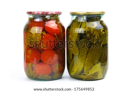 Two clear glass jars of colorful pickled vegetables: tomatoes and cucumbers - stock photo