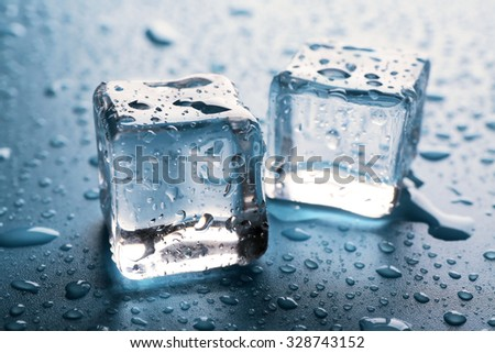 Two clear melting ice cubes with drops around, close up - stock photo