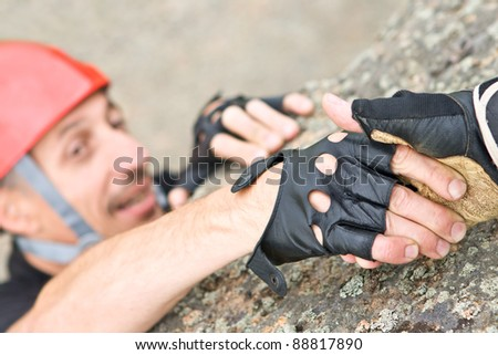 Two climbers keeping capture by hands in mountains - stock photo