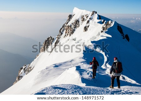Two climbers on a snow ridge in the Alps