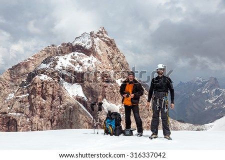 Two Climbers on Snow Pass Tall and Short Men with Climbing Gear and Expedition Clothing Backpacks on Glacier with High Steep Rock Peak and Stormy Sky on Background - stock photo