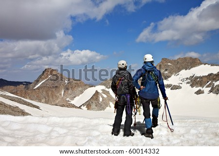 Two climbers on the mountain pass looking at the mountains - stock photo