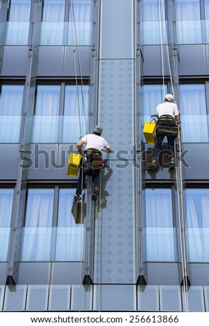 Two climbers wash windows and glass facade of the skyscraper  - stock photo