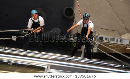 Two Climbers Working on Heights. Workers hanging on climbing ropes, showing thumb up sign. - stock photo