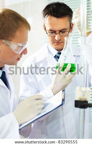 Two clinicians studying new substance and interacting in laboratory